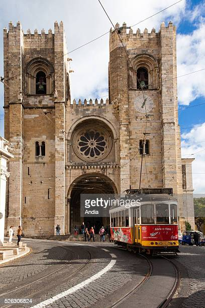 an old red tram on line nr 28 passes by Santa Maria Maior of Lisbon cathedral It is the oldest church in the city November 2012