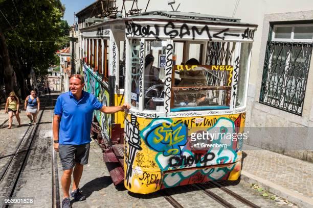 Portugal Lisbon Bairro Alto Elevador da Gloria funicular railway tram with graffiti man posing
