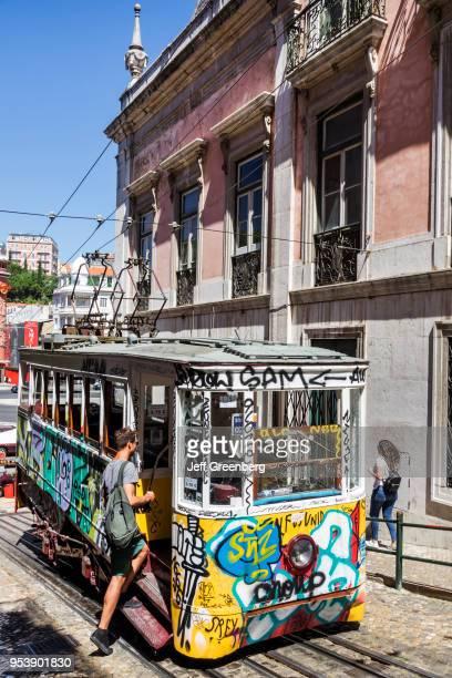 Portugal Lisbon Bairro Alto Elevador da Gloria funicular railway tram with graffiti man boarding