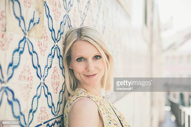 Portugal, Lisbon, portrait of smiling blond woman leaning against wall with Azulejos