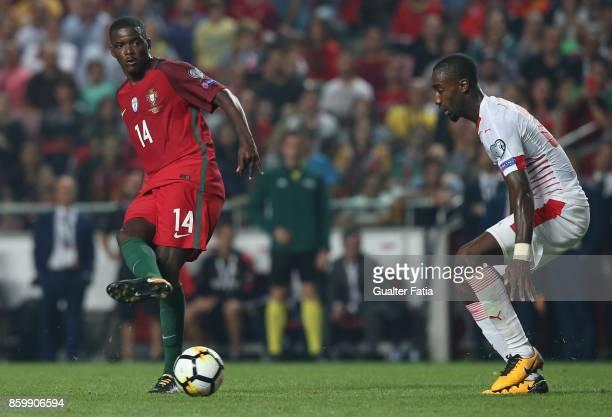 Portugal midfielder William Carvalho with Switzerland defender Johan Djourou in action during the FIFA 2018 World Cup Qualifier match between...