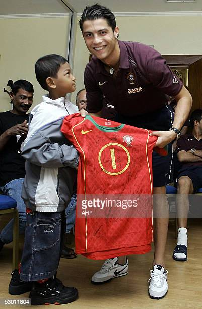 Portugal national soccer team and Manchester United striker Cristiano Ronaldo poses with Martunis a 7yearold Indonesian tsunami survivor in Lisbon 02...