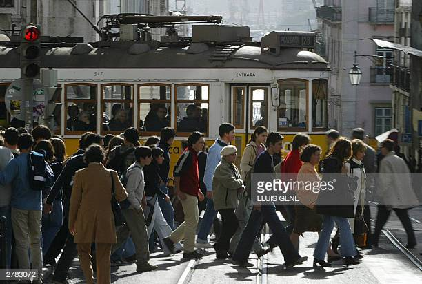 Picture taken 28 November 2003 in Lisbon showing people crossing in front of the tramway on the Rua do Alecrim in the center of the Portuguese...