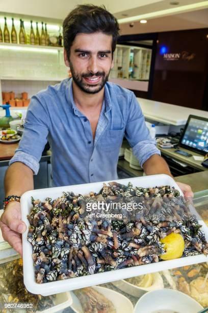 Portugal, Porto, Mercado do Bom Sucesso, vendor with tray of Goose Barnacles.