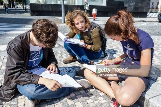 Portugal, Porto, Praca Bom Sucesso, teens filling out survey questionnaire.