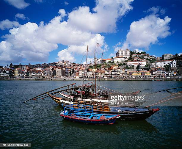 Portugal, Porto, Rabelo boats in port with city skyline