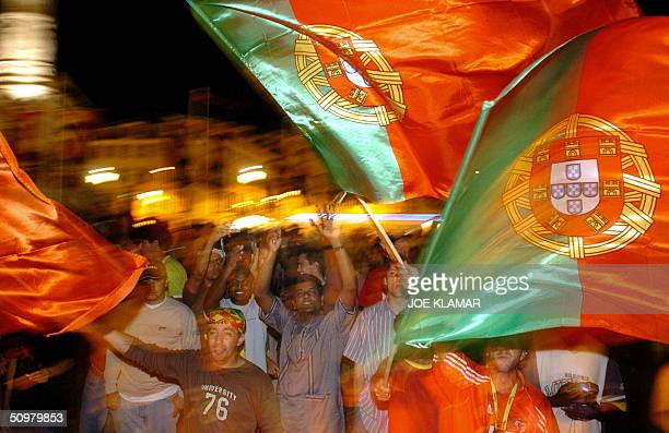 Portugese football supporters wave national flags as they celebrate their team's victory in the heart of the old town at Rossio square in Lisbon 20...