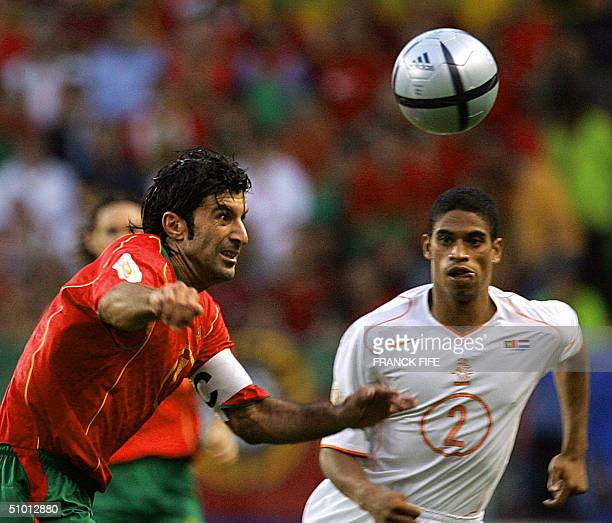 Portuguese captain Luis Figo watches the ball as Dutch defender Michael Reiziger watches him 30 June 2004 at the Alvalade stadium in Lisbon during...
