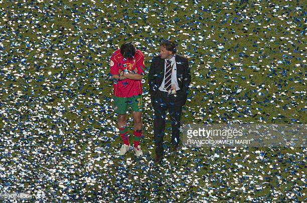Portuguese defender Paulo Ferreira is comforted by the team's press officer04 July 2004 at Stadio da Luz in Lisbon after the Euro 2004 final football...