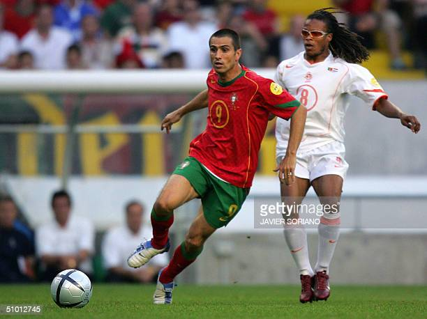 Portuguese forward Pedro Miguel Pauleta runs past Dutch midfielder Edgar Davids 30 June 2004 at the Alvalade stadium in Lisbon during the Euro2004...