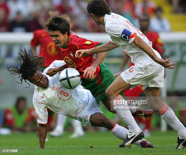 Portuguese midfielder Deco is tackled by Dutch midfielder Edgar Davids 30 June 2004 at the Alvalade stadium in Lisbon during the Euro2004 semifinal...