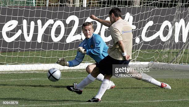 Russian forward Dmitry Alenichev scores in front of goalkeeper Igor Akinfeev during a training session at the Browns club and resort hotel in...