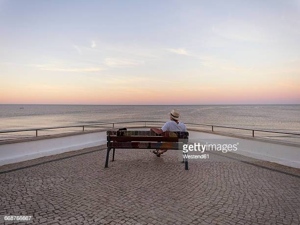 Portugal, Senior man siting on bench watching sunrise