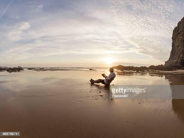 portugal, senior man sitting at beach, reading book - só um homem imagens e fotografias de stock