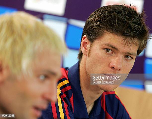 Spanish midfielder Xabi Alonso looks at his teammate goalkeeper Santiago Canizares during a press conference at the end of a team training session at...