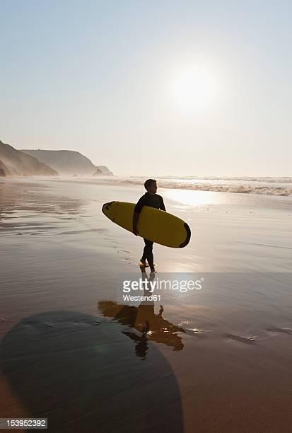 Portugal, Surfer walking on beach