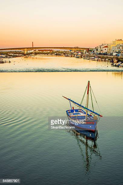 Portugal, Tavira, Fishing boat on river with town in background