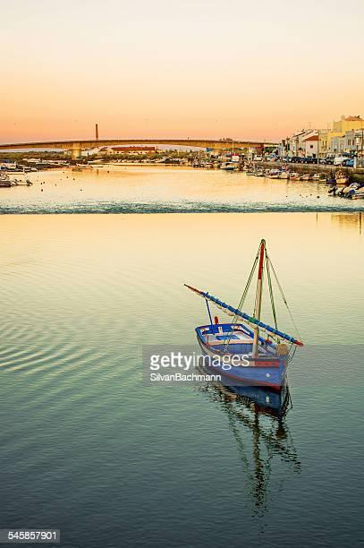 portugal, tavira, fishing boat on river with town in background - tavira imagens e fotografias de stock