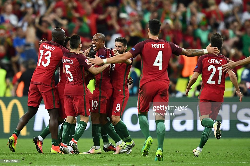 Portugal team players celebrate as they clinch the match 1-0 against France in the Euro 2016 final football match between France and Portugal at the Stade de France in Saint-Denis, north of Paris, on July 10, 2016. / AFP / FRANCK
