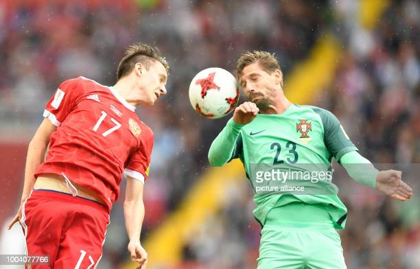 Portugal's Adrien Silva and Russia's Alexander Golovin vie for the ball during the preliminary stage group A match between Russia and Portugal in the...