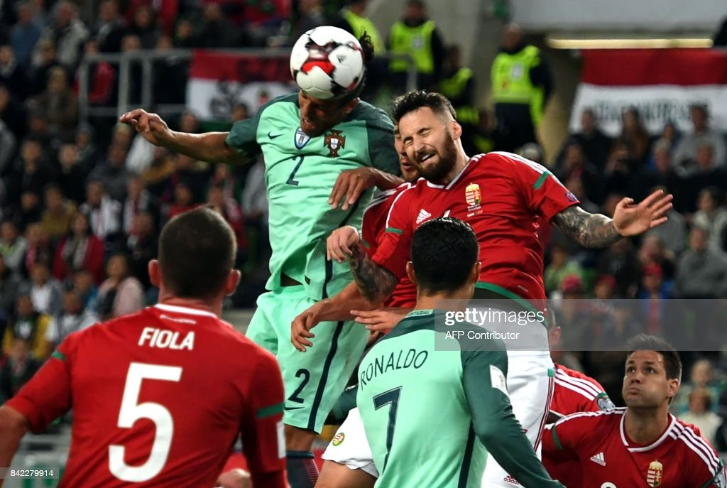 Portugal's Bruno Alves (C/L) fights for the ball with Hungary's Tamas Kadar (C/R) during the FIFA World Cup 2018 qualification football match between Hungary and Portugal at The Grupama Arena in Budapest on September 3, 2017. /