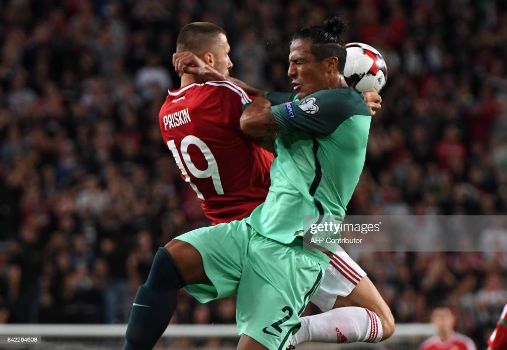 Portugal's Bruno Alves (R) vies with Hungary's Tamas Priskin during the FIFA World Cup 2018 qualification football match between Hungary and Portugal in Budapest on September 3, 2017. /