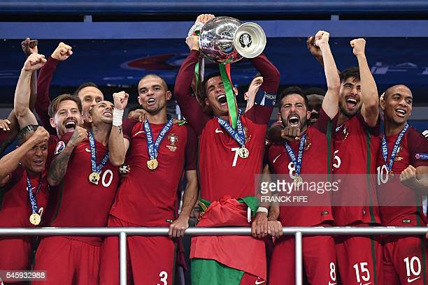 TOPSHOT Portugal's captain and forward Cristiano Ronaldo hold up the winners' trophy in the Euro 2016 final football match between France and...