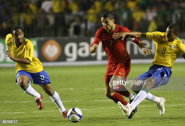 Portugal's Cristiano Ronaldo vies for the ball with Brazil's Gilberto Silva and Anderson during their friendly football match at Bezerrao Stadium in...