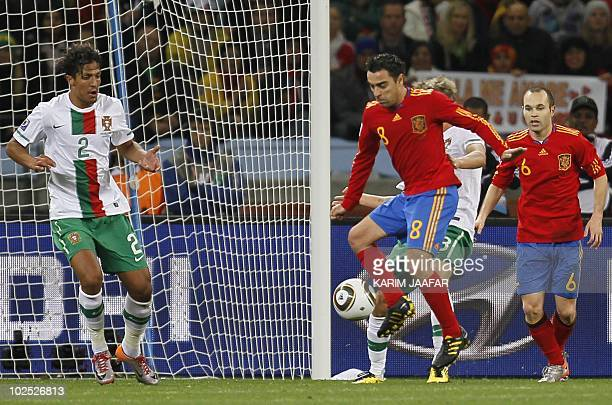 Portugal's defender Bruno Alves and Spain's midfielder Xavi and Spain's midfielder Andrés Iniesta fight for the ball during the 2010 World Cup Round...