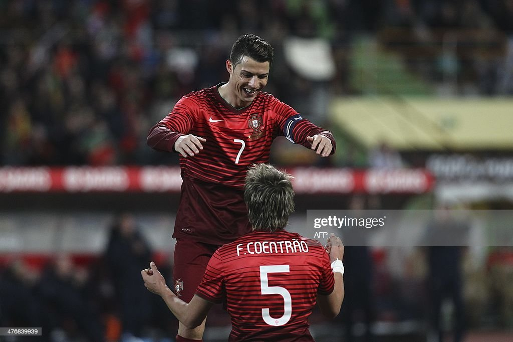 Portugal's defender Fabio Coentrao (R) celebrates with his teammate Portugal's forward Cristiano Ronaldo after scoring during the FIFA 2014 World Cup friendly football match Portugal vs Cameroon at Magalhaes Pessoa stadium in Leiria on March 5, 2014.
