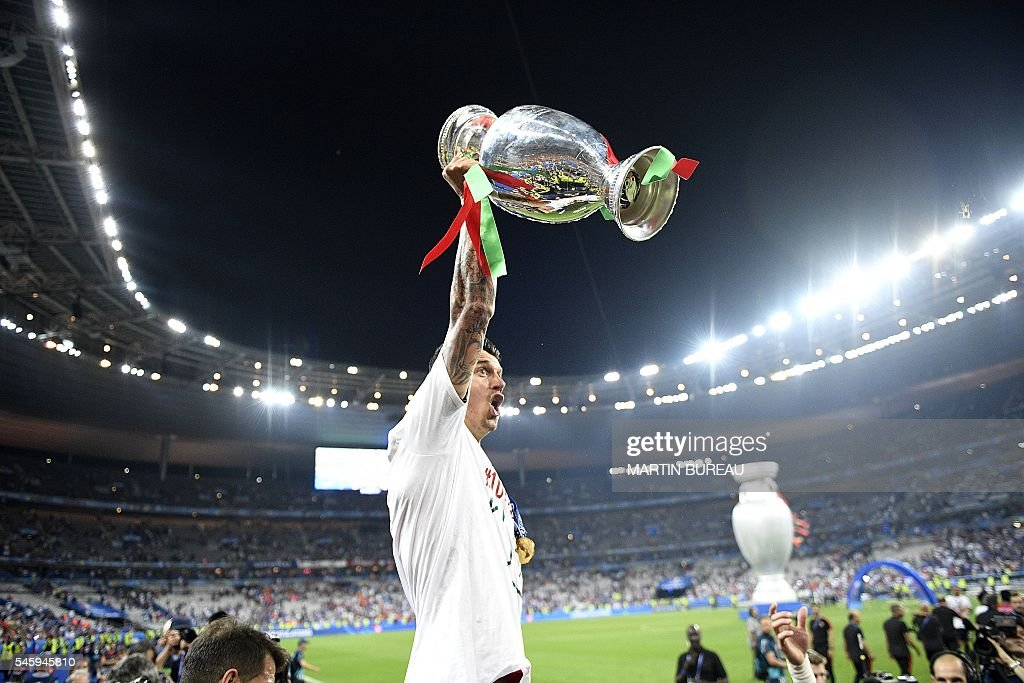 Portugal's defender Fonte holds up the winners' trophy as he celebrates with teammates after beating France 1-0 to clinch the Euro 2016 final football match between France and Portugal at the Stade de France in Saint-Denis, north of Paris, on July 10, 2016. / AFP / MARTIN