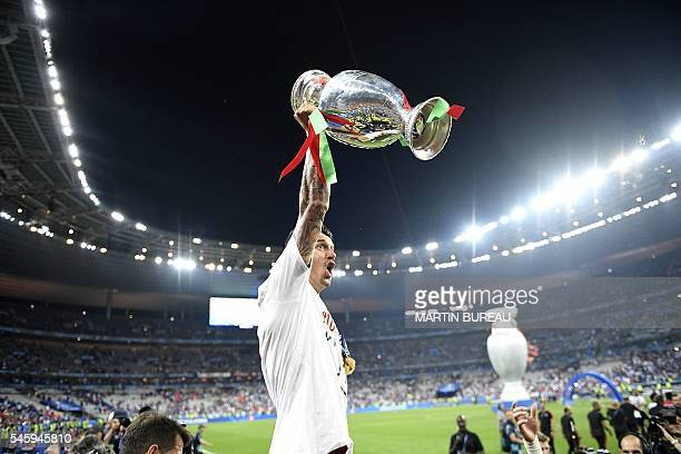 Portugal's defender Fonte holds up the winners' trophy as he celebrates with teammates after beating France 10 to clinch the Euro 2016 final football...