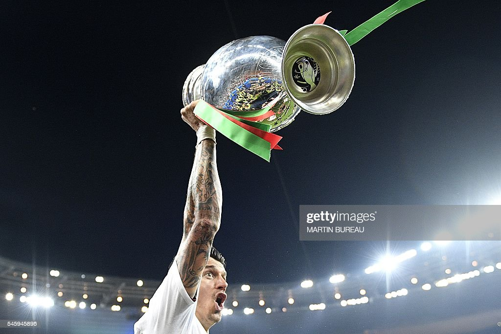 TOPSHOT - Portugal's defender Fonte holds up the winners' trophy as he celebrates with teammates after beating France 1-0 to clinch the Euro 2016 final football match between France and Portugal at the Stade de France in Saint-Denis, north of Paris, on July 10, 2016. / AFP / MARTIN