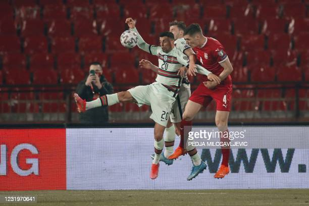 Portugal's defender Joao Cancelo fights for the ball with Serbia's defender Nikola Milenkovic during the FIFA World Cup Qatar 2022 qualification...