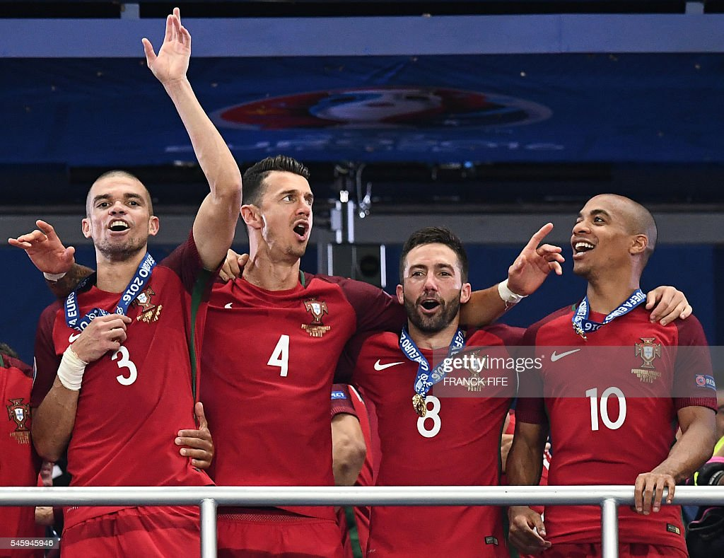 Portugal's defender Pepe (L), Portugal's defender Fonte, Portugal's midfielder Joao Moutinho and Portugal's midfielder Joao Mario (R) celebrate as they arrive to collect the winners' trophy after beating France 1-0 to clinch the Euro 2016 final football match between France and Portugal at the Stade de France in Saint-Denis, north of Paris, on July 10, 2016. / AFP / FRANCK