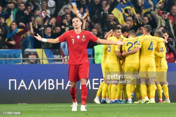 Portugal's defender Pepe reacts as Ukraine's players celebrate a goal during the Euro 2020 football qualification match between Ukraine and Portugal...