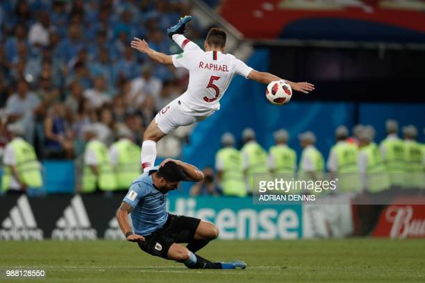 TOPSHOT Portugal's defender Raphael Guerreiro collides with Uruguay's forward Luis Suarez during the Russia 2018 World Cup round of 16 football match...