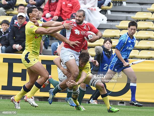 Portugal's Duarte Moreira is tackled by Australia's Pama Fou and Con Foley during their match at the Tokyo Rugby Sevens in Tokyo on April 4, 2015....