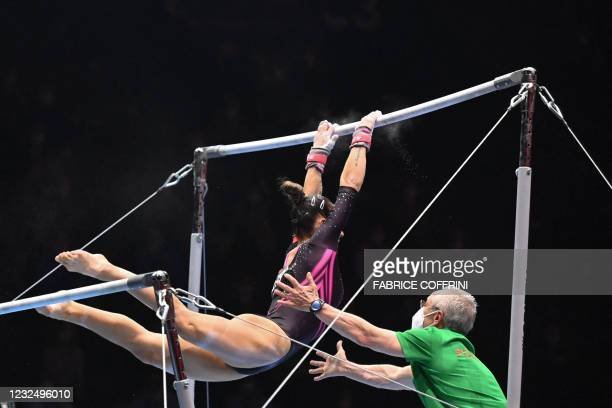 Portugal's Filipa Martins is helped by her coach as she competes in the Women's uneven bars apparatus final of the 2021 European Artistic Gymnastics...