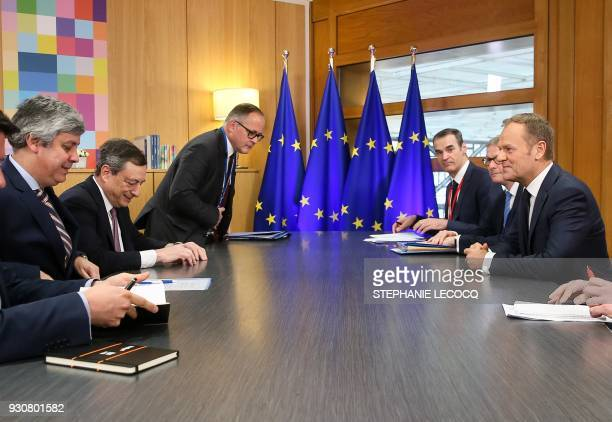 Portugal's Finance Minister and Eurogroup President Mario Centeno and Mario Draghi President of the European Central Bank speak with European Council...
