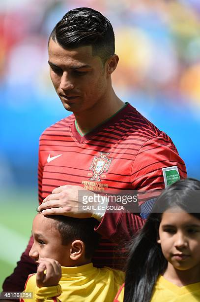 Portugal's forward and captain Cristiano Ronaldo hugs a child on the pitch during the lineup prior to the Group G football match between Portugal and...