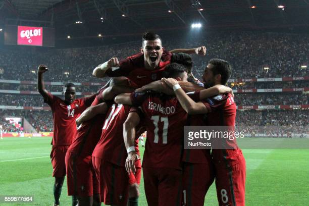 Portugal's forward Andre Silva celebrates with teammates after scoring during the 2018 FIFA World Cup qualifying football match between Portugal and...