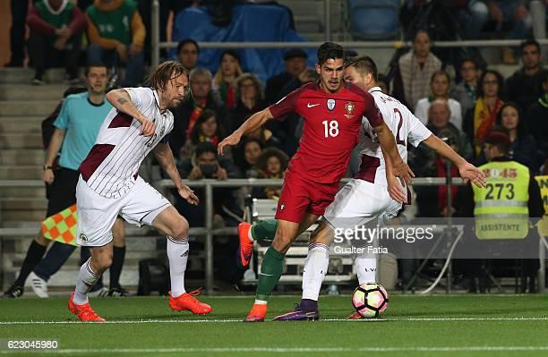 Portugal's forward Andre Silva with Latvia's defender Kaspars Gorses from Latvia and Latvia's defender Vitalijs Maksimenko from Latvia in action...