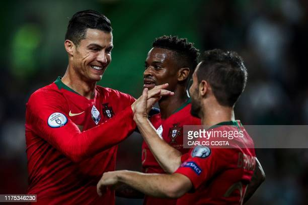 Portugal's forward Bernardo Silva celebrates with Portugal's forward Cristiano Ronaldo and Portugal's defender Nelson Semedo after scoring a goal...