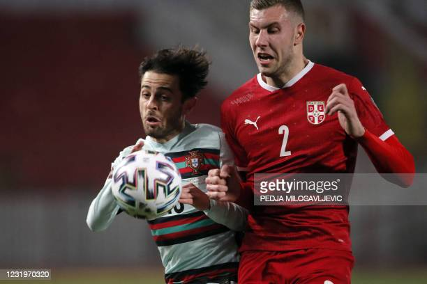 Portugal's forward Bernardo Silva fights for the ball with Serbia's defender Strahinja Pavlovic during the FIFA World Cup Qatar 2022 qualification...