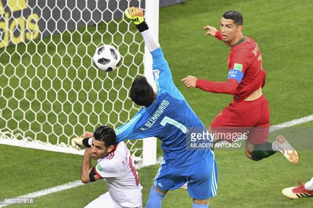 TOPSHOT Portugal's forward Cristiano Ronaldo and Iran's goalkeeper Alireza Beiranvand vie for the ball during the Russia 2018 World Cup Group B...