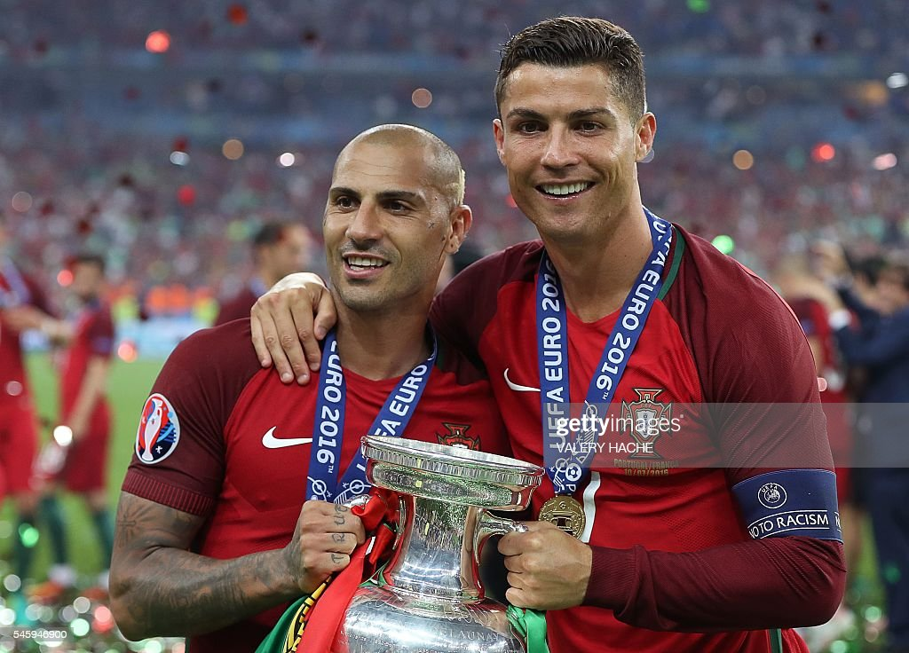Portugal's forward Cristiano Ronaldo (R) and Portugal's forward Ricardo Quaresma pose with the trophy as they celebrate after beating France during the Euro 2016 final football match at the Stade de France in Saint-Denis, north of Paris, on July 10, 2016. / AFP / Valery HACHE