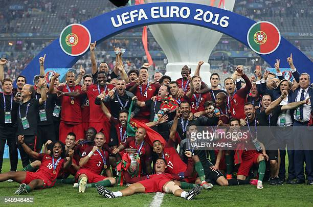Portugal's forward Cristiano Ronaldo and teammates pose with the trophy as they celebrate after beating France during the Euro 2016 final football...
