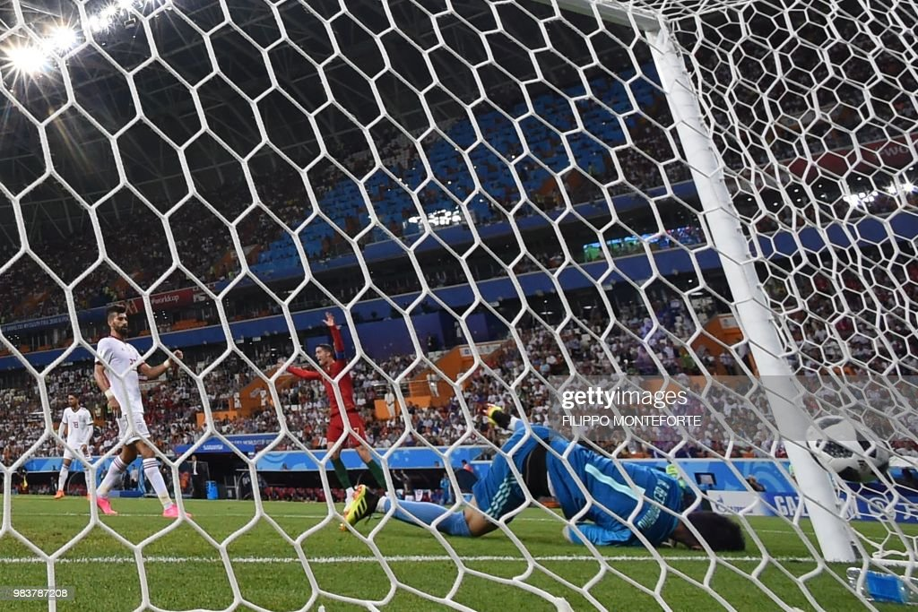 TOPSHOT - Portugal's forward Cristiano Ronaldo (R) celebrates after Portugal's forward Ricardo Quaresma scored the opening goal past Iran's goalkeeper Alireza Beiranvand (R) during the Russia 2018 World Cup Group B football match between Iran and Portugal at the Mordovia Arena in Saransk on June 25, 2018. (Photo by Filippo MONTEFORTE / AFP) / RESTRICTED