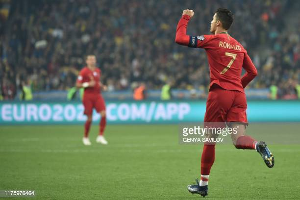 TOPSHOT Portugal's forward Cristiano Ronaldo celebrates after scoring a goal from the penalty spot during the Euro 2020 football qualification match...